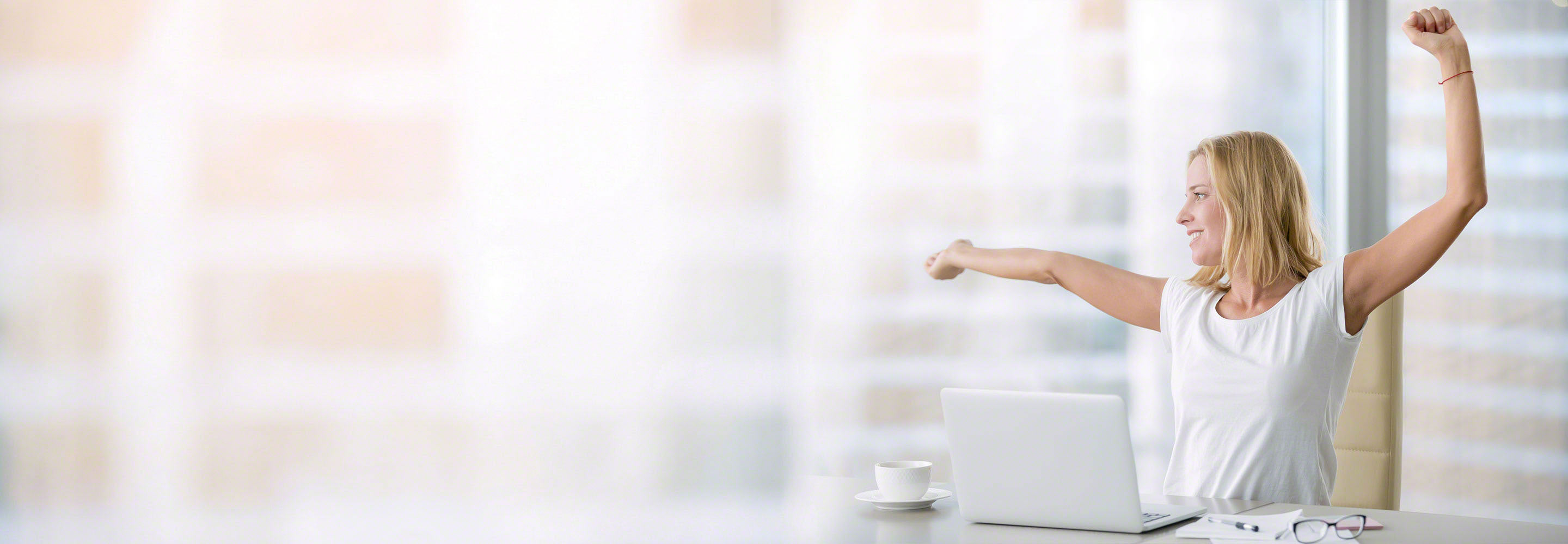 Woman looking out office window while stretching