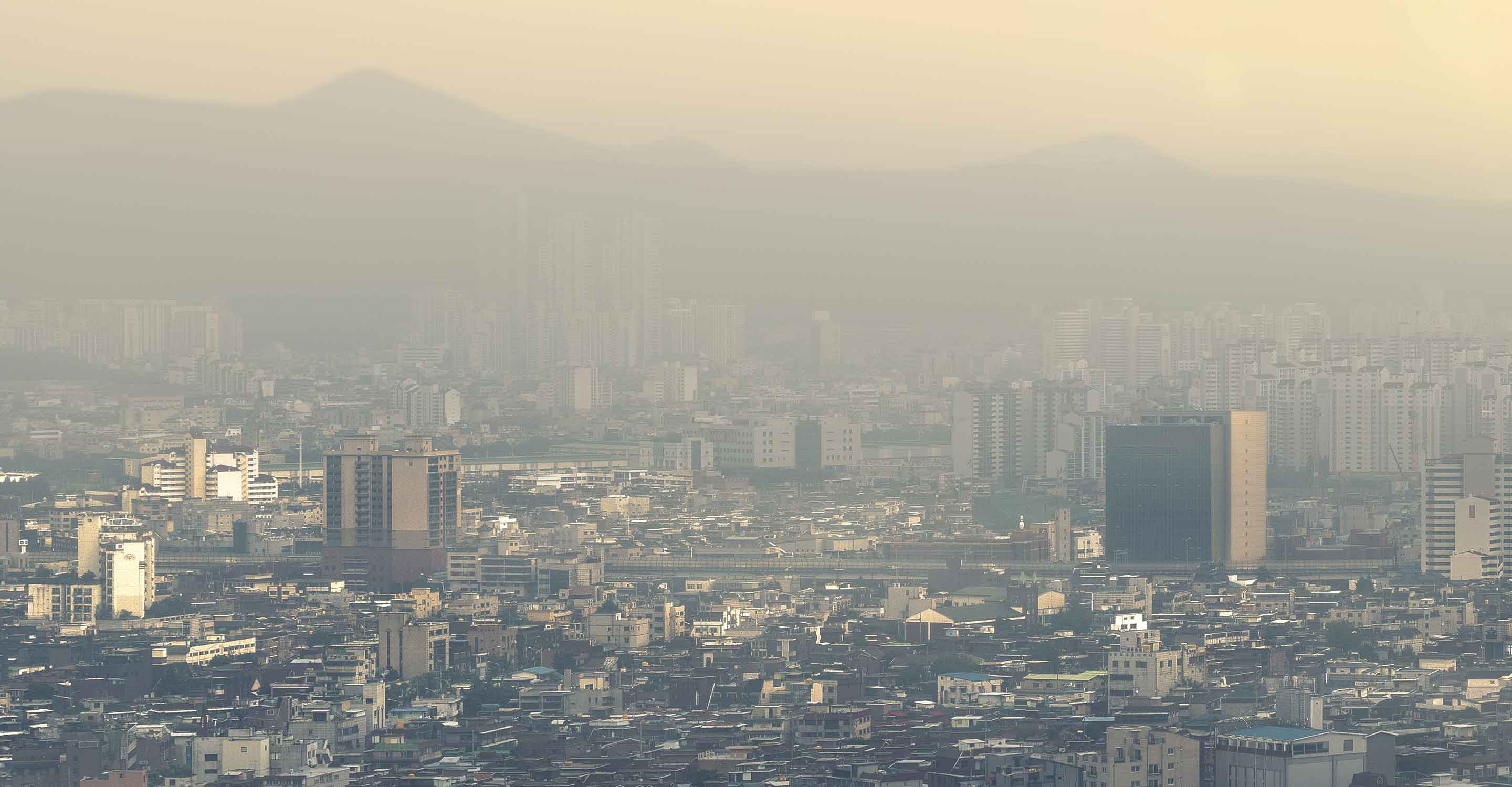 An image of a city skyline with visible smog obscuring anything beyond a couple of miles' visibility.