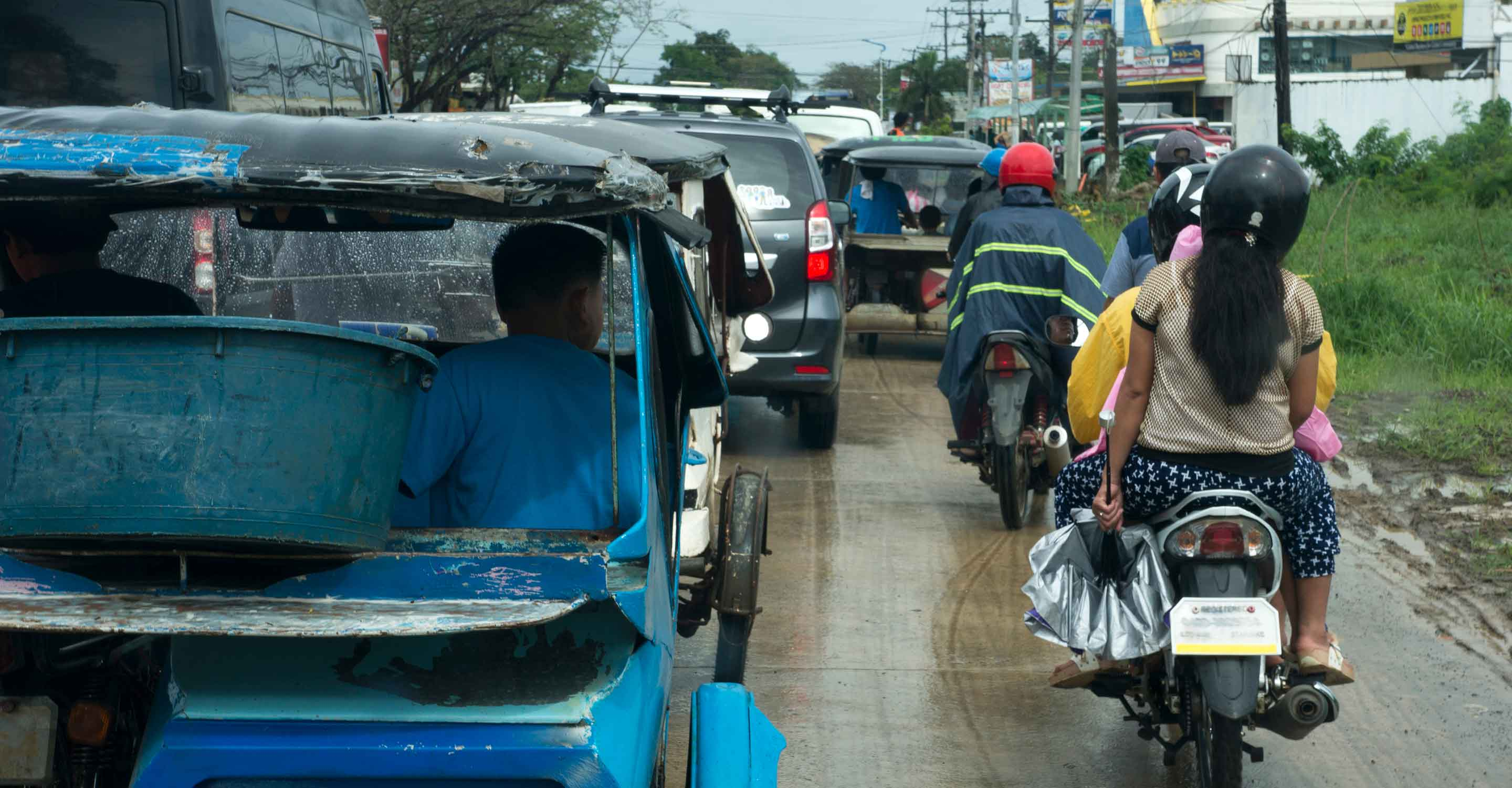 Filipino/a drivers on motorcycles and in cars on a wet, congested road in what is ostensibly the Philippines.