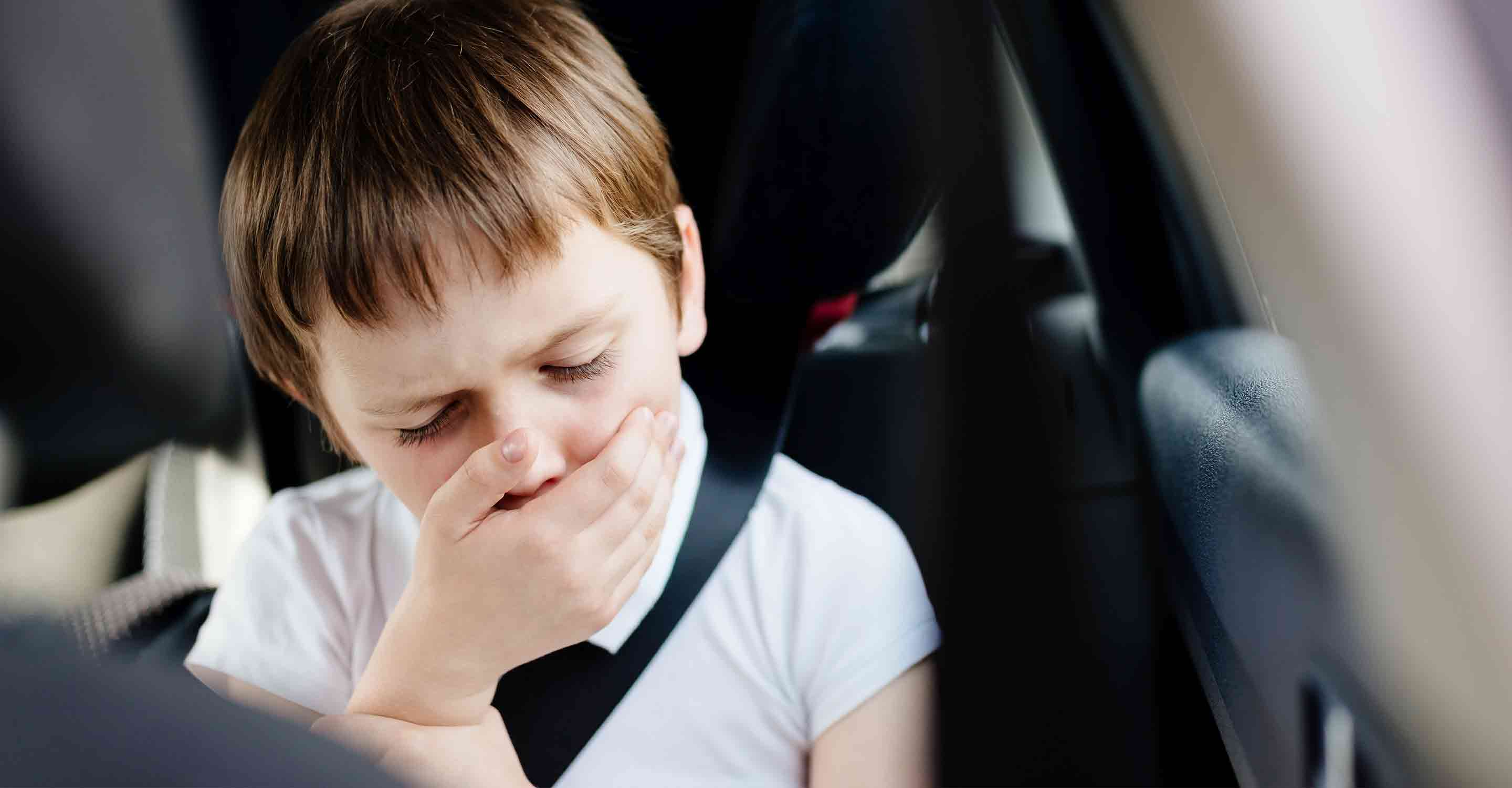 Kid coughing in the back seat of a car