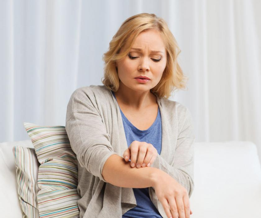 Lady touching arm with dry skin