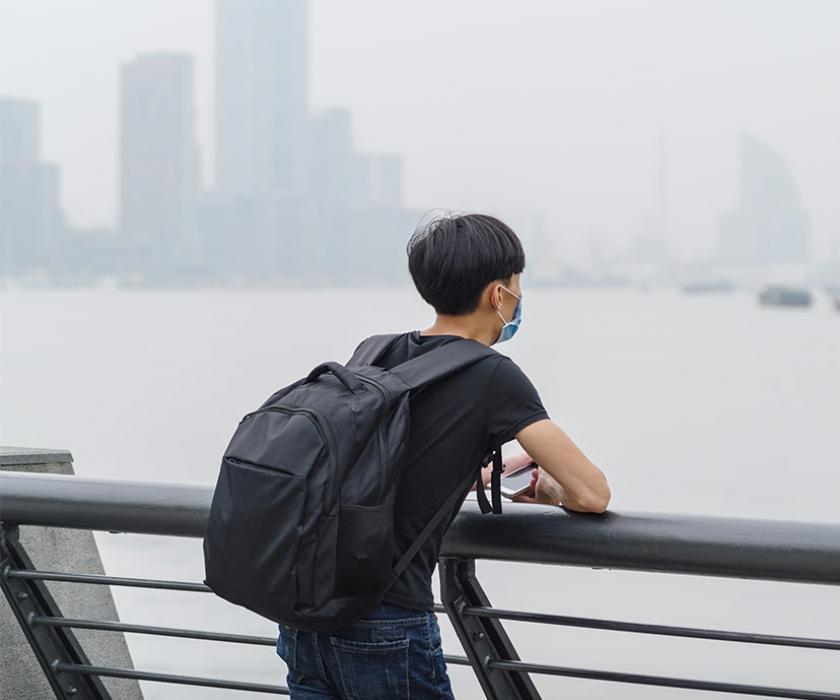 A young man wearing a dust mask looks out across the harbor of a major city, its skyline in the distance, that appears shrouded in a polluted haze.