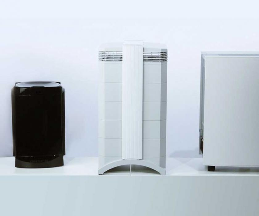 Three air purifiers positioned in a row.