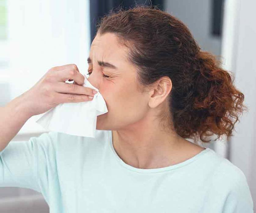 Woman with allergies blows her nose